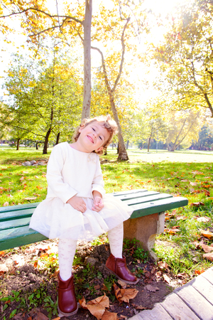Portrait of positive child sitting on the bench in park photo