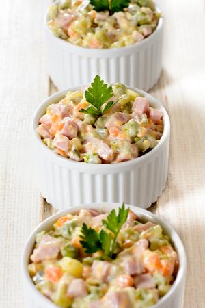 huzarensalade: Russische salade in witte kopjes, selectieve aandacht Stockfoto