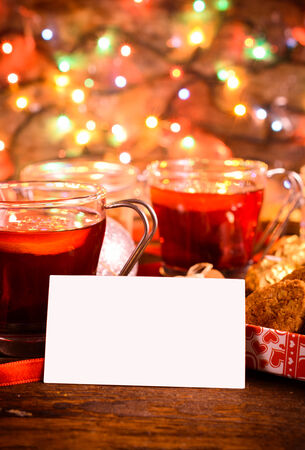 Blank white card with tea and cookies in background,selective focus photo