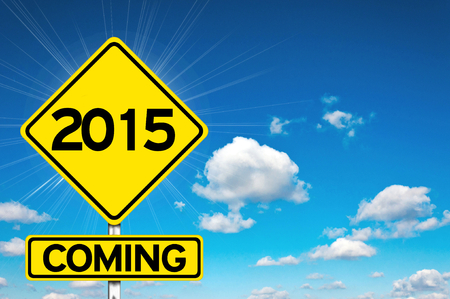 2015 coming sign yellow road sign with clouds and sky in background photo