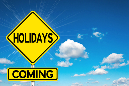 Holidays coming sign yellow road sign with clouds and sky in background photo