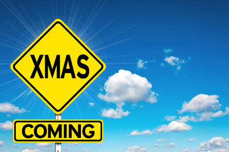 Xmas coming sign yellow road sign with clouds and sky in background photo