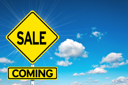 Sale coming sign yellow road sign with clouds and sky in background photo