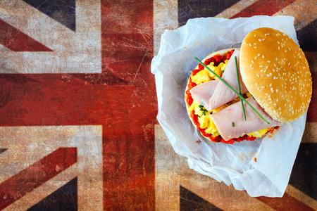 uk cuisine: Scrambled egg in bun with ajvar salad and ham on British flag,selective focus