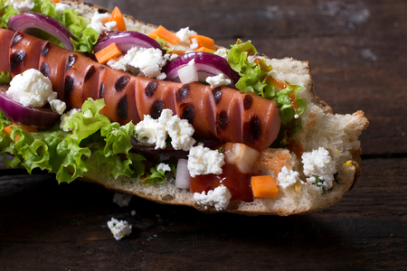 Grilled hot dog with cheese and vegetables,selective focus photo