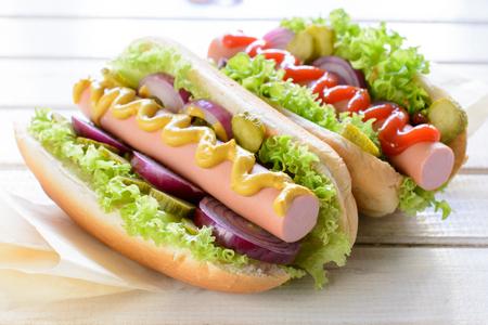 comida alemana: Perritos calientes cl�sicos con la mostaza y la salsa de tomate en el fondo de madera, enfoque selectivo Foto de archivo