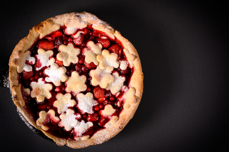 Red berry pie from above on the dark background with blank space on right side photo