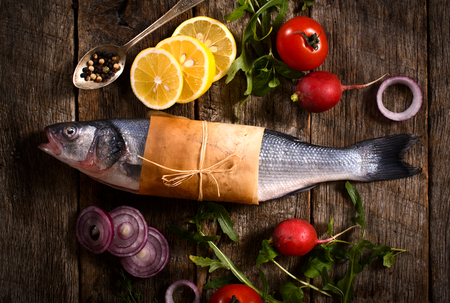 Raw bass fish with vegetables from above on the wooden background Banco de Imagens