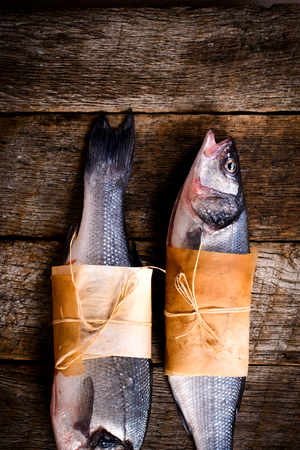 smal: Two raw bass fish on wooden background and blank space Stock Photo