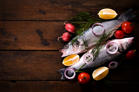 frozen fish: Fresh bass fish on the wooden background with blank space Stock Photo