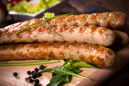 close p: Close p to grilled sausages on wooden board,selective focus