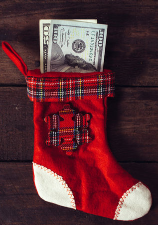 Traditional Christmas sock with the money on wooden wall