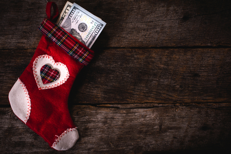Traditional Christmas sock with the money on wooden wall with blank space