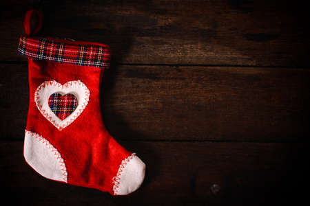 Red and white traditional Christmas sock on wooden background with blank space photo