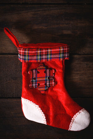 Empty traditional red and white Christmas sock on wooden background photo