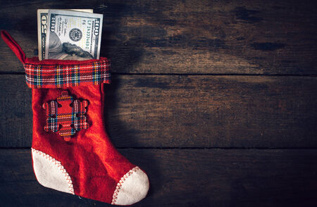 Traditional Christmas sock with the money on wooden wall photo