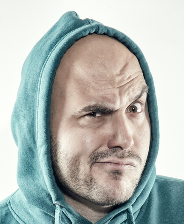 rolled up sleeves: Suspicious man with hood on his bald head