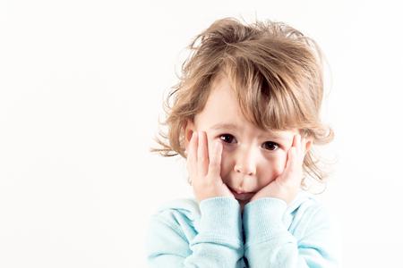 comprehend: Portrait of worried child on white background