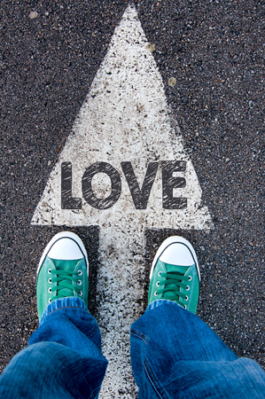 active arrow: Green shoes standing on your love sign Stock Photo