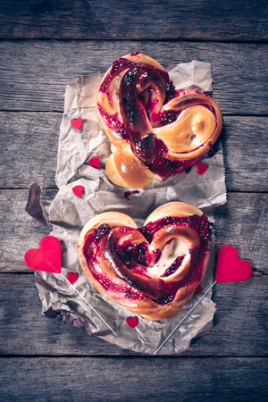 cherry: Heart shape pastries stuffed with cherry jelly on wooden background