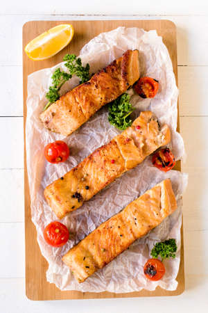Prepared salmon fish fillets and grilled tomato,selective focus photo