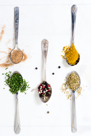 herbs white background: Group of spices in the spoons from above on wooden background