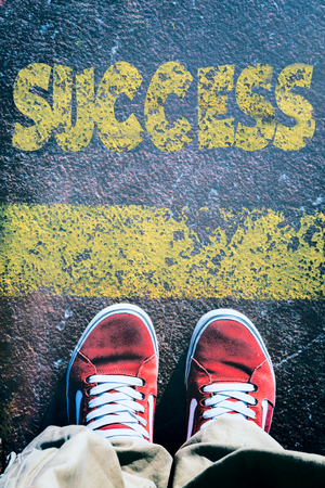 definition define: Mans legs behind the yellow line from above with success sign Stock Photo
