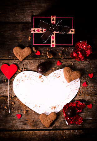 St. Valentine decoration with blank heart shape paper on wooden bacground photo