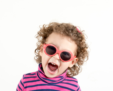 happines: Positive child with retro sunglasses showing her happines Stock Photo