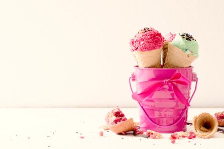 cono de helado: Helados en la cesta de color rosa y el espacio en blanco en el lado izquierdo, el enfoque selectivo y alto clave Foto de archivo