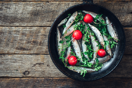 smelt: Smelt fishes in old pan on wooden background with blank space Stock Photo