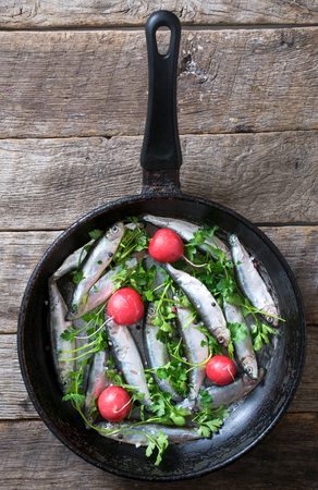 freisteller: Smelts fish in the pan on wooden background