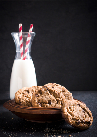 chocolate chip cookies: Sweet chocolate chip cookies and bottle of milk,selective focus