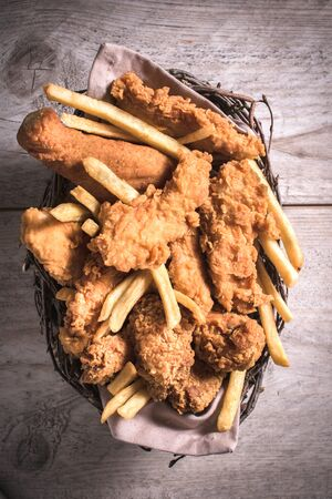 Fried chicken meat and French fries from above in the basket Foto de archivo