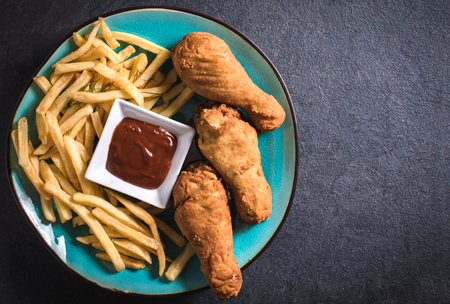 food and beverages: French fries and fried chicken legs on dark background with blank space