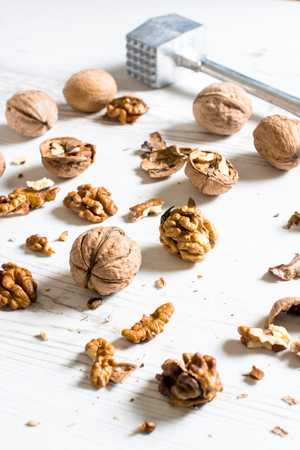 splashed: Splashed raw walnuts and metal hammer on wooden background,selective focus Stock Photo