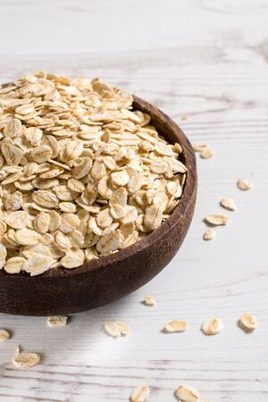 flaked: Organic oat flaked in the wooden bowl,blank space