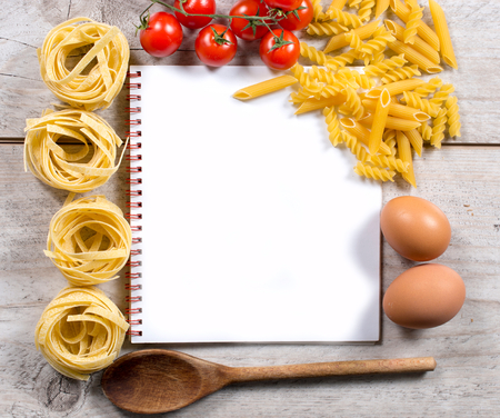 Blank cook book with set up for preparing traditional Italian cuisine,above and wooden background