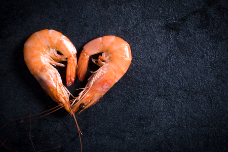 Boiled tiger shrimps heart shape on table with blank space on the right side Stock Photo