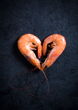 Heart shape boiled tiger shrimps on dark background with blank space