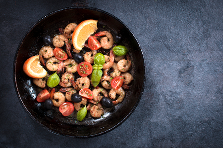 aphrodisiac: Fried tiger shrimps with ingredients in the pan from above on dark background with blank space Stock Photo