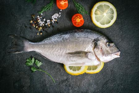 dorado fish: Raw dorada fish with ingredients on dark background Stock Photo