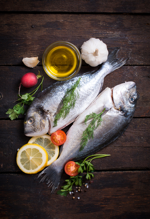 sparus: Raw dorada fish with ingredients on wooden background Stock Photo