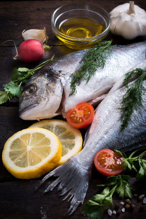overfishing: Raw dorada fish with ingredients on wooden background,selective focus Stock Photo