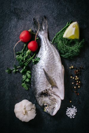 Raw glithead fish with ingredients from above on dark background Stock Photo