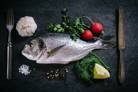 demersal: Raw glithead fish with ingredients from above on dark background Stock Photo