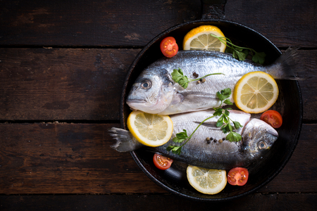 gilthead bream: Glithead fishe in pan with ingredients on wooden background with blank space