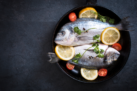 gilthead bream: Raw fish with ingredients in the pan on dark background with blank space