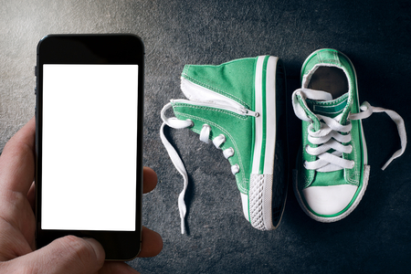 Fashionable green sneakers for kids nad blank white screen on the smart phone photo