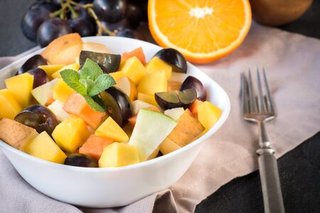 fruity salad: Fresh salad with sliced tropical fruits in the bowl,selective focus